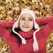 Happy woman laying on Autumn leaves — Stock Photo #14545817
