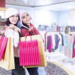 Shopaholic friends holding bags in the mall — Stock Photo