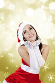 Blowing snowflakes by Mrs. Clause in golden lights — Stock Photo
