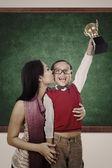 Boy raising trophy kiss by his mother in class — Zdjęcie stockowe