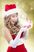 Happy santa woman receive christmas gift on golden lights — Stok fotoğraf