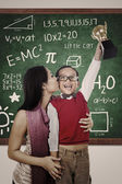 Preschooler wins Math competition holding trophy kiss by mum — ストック写真