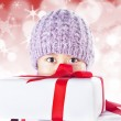 Boy behind gifts on red defocused lights background — Stock Photo #14777691
