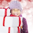 Happy boy holding white christmas boxes on defocused light — Стоковая фотография