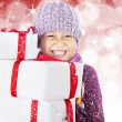 Happy boy holding white christmas boxes on defocused light — Foto Stock
