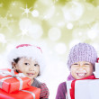 Brother and sister open christmas gifts on defocused lights — Stock Photo