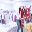 Happy friends shopping with trolley at the mall — Stock Photo