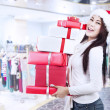 Holding christmas boxes with santa hat at mall — Stock Photo