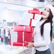 Holding christmas boxes with santa hat at mall — Stock Photo #14917207