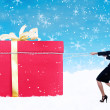 Business woman pull Christmas gift in snow with chain — Stock Photo