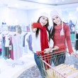Happy friends shopping with gift card and trolley — Stock Photo