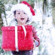 Asian girl with Santa hat holding red gifts — Foto Stock