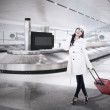 Beautiful woman collect luggage at airport — Stock Photo #15897719