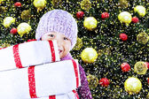 Boy with christmas gifts under tree — Stock Photo