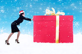 Businesswoman push christmas gift in snow — Stock Photo