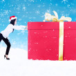 Christmas gift pushed by woman on blue background — Stock Photo #15921805