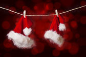 Two Christmas Santa hats hanging on red defocused lights — Stock Photo