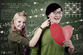 Beautiful nerd girl and guy in love at school — Stock Photo