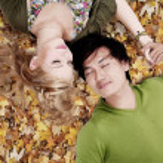 Beautiful loving couple sleep on autumn leaves — Stock Photo #16277383
