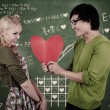 Cute nerd guy and girl holding heart in classroom — Stock Photo