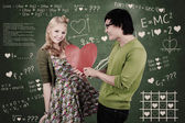 Cute nerd guy and girl giving love in class — Stock Photo