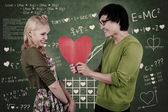 Cute nerd guy and girl holding heart in classroom — Stok fotoğraf