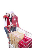 Happy winter shopping trolley with friend isolated — Zdjęcie stockowe