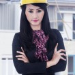 Beautiful engineer standing outdoor with yellow helmet — Stock Photo