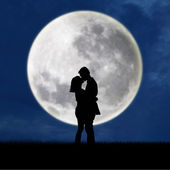 Close up of silhouette couple kissing on full moon — 图库照片