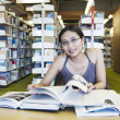 Attractive female student study at library — Stock Photo