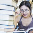 Happy student reading books in library — Stock Photo #16359559