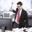 Angry businessman throw hammer at computer — Stock Photo