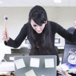 Angry businesswoman with hammer and laptop - Foto Stock