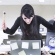 Stock Photo: Angry businesswoman with hammer and laptop