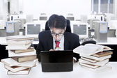 Businessman surrounded with books and computer — Stock Photo