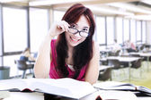 Female student reading with glasses — Stock Photo