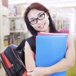 Stock Photo: Beautiful womwith bag and folder in library