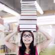 Foto Stock: Girl student carry books on head