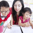 Mother teach children to write — Stock Photo #17038373