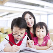 Stock Photo: Mother encourage children to be creative