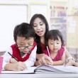 Stock Photo: Teacher and children study in classroom