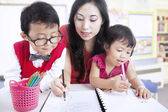 Mother teach children to write — Stock Photo