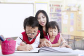Teacher and children study in classroom — 图库照片