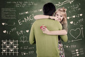 Happy couple hugging in class — Stock Photo