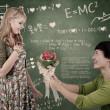 Beautiful nerd girl get flowers in class — Stock Photo