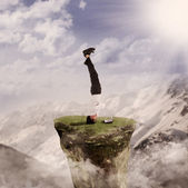 Businessman handstand with laptop by nature — Zdjęcie stockowe