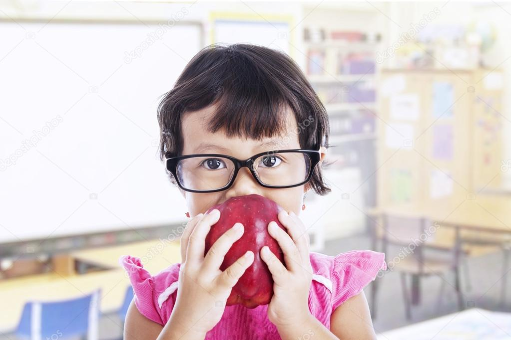 Portrait of asian female preschooler eating red apple at class — Stock Photo #18537165