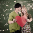 Cute couple with valentine heart card — Stock Photo