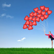 Foto Stock: Girl hold red heart balloons