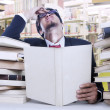 Stress businessman and stack of books - Zdjęcie stockowe